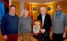 El tallista Velázquez Arquelladas regala el escudo de Huétor Vega a la Bodega Vicente Márquez