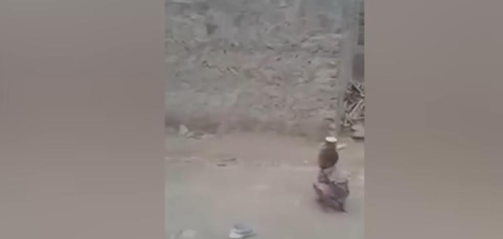 Un niño dispara con un rifle contra una lata sobre la cabeza de su amigo