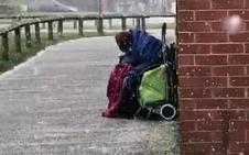 La foto de un anciano indigente hecho un ovillo bajo la nieve agita conciencias