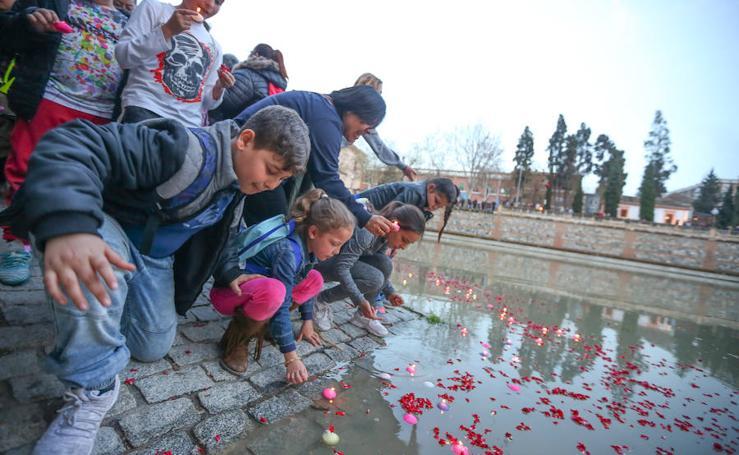 Velas encendidas y pétalos de flores en el Genil para honrar al pueblo gitano