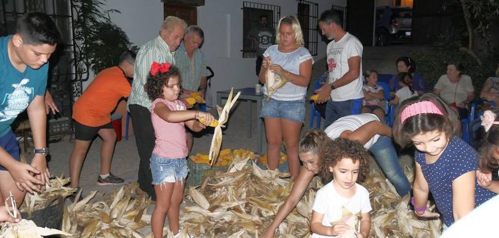 Varias generaciones se unen en La Alquería para desgranar el maíz