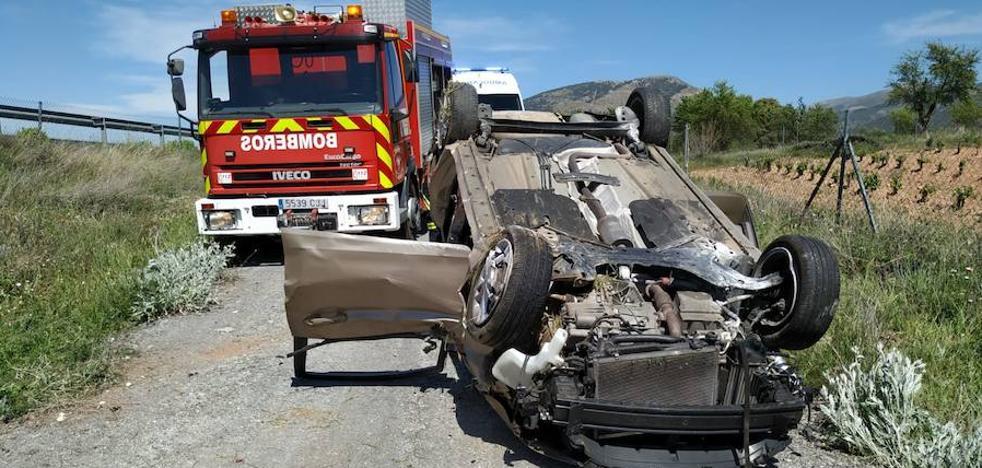 Sofocan un incendio y rescatan al ocupante herido de un vehículo accidentado en Guadix