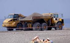 Los primeros bañistas toman el sol entre excavadoras en Motril