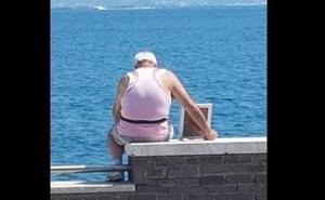 La entrañable historia tras la foto del anciano que lleva el retrato de su esposa muerta al mar