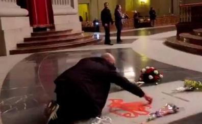 Un hombre pinta de rojo la tumba de Franco