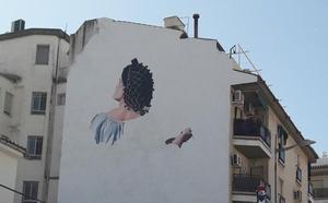 El artista José Ríos pinta un mural de María Bellido en una fachada de Bailén