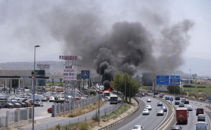 Un autobús ardiendo en plena autovía en Granada, visto desde la misma carretera