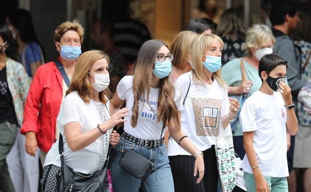 Un grupo de personas lleva mascarilla en la calle./EFE