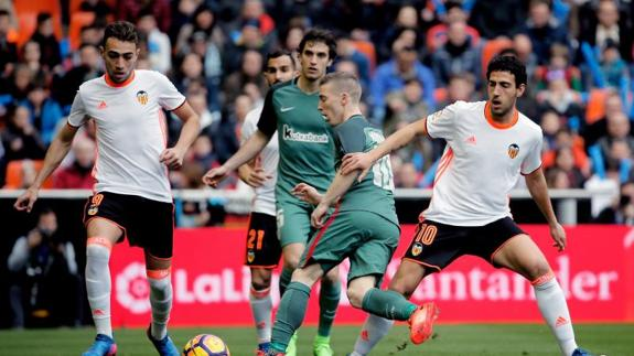 Muniain conduce ante Parejo y Munir. /
